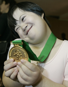 A Special Olympics lovingly holds up her medal.